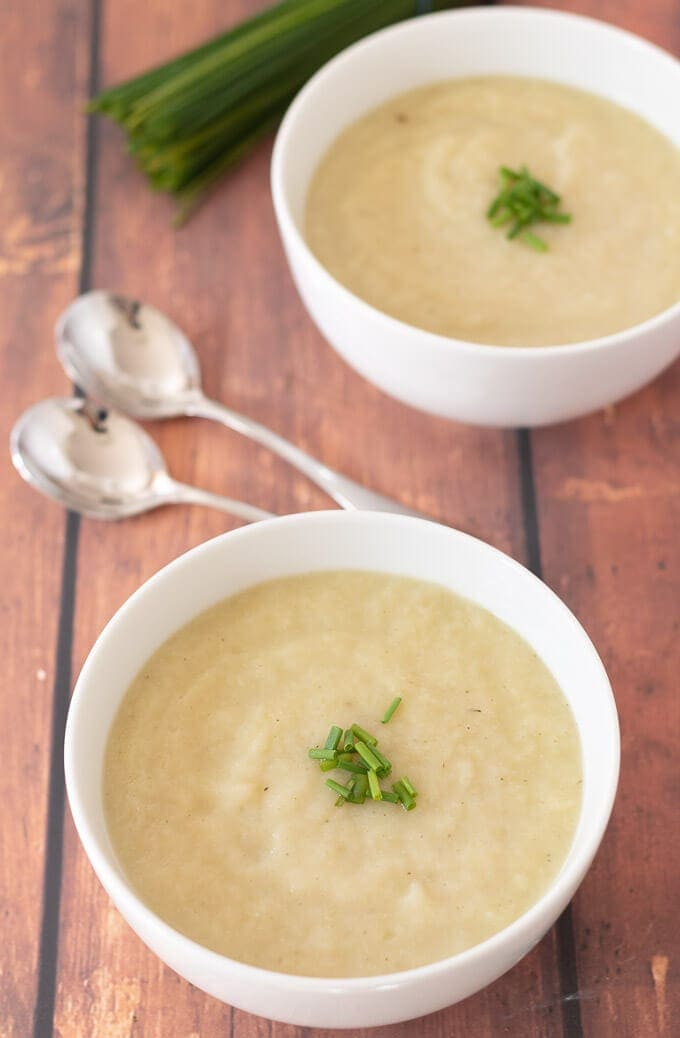Delicious bowls of creamy vegan cauliflower leek soup garnished with chives served and ready to eat.