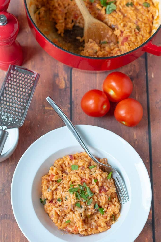 Tomato and basil risotto served in a white pasta bowl with fork in ready to eat.