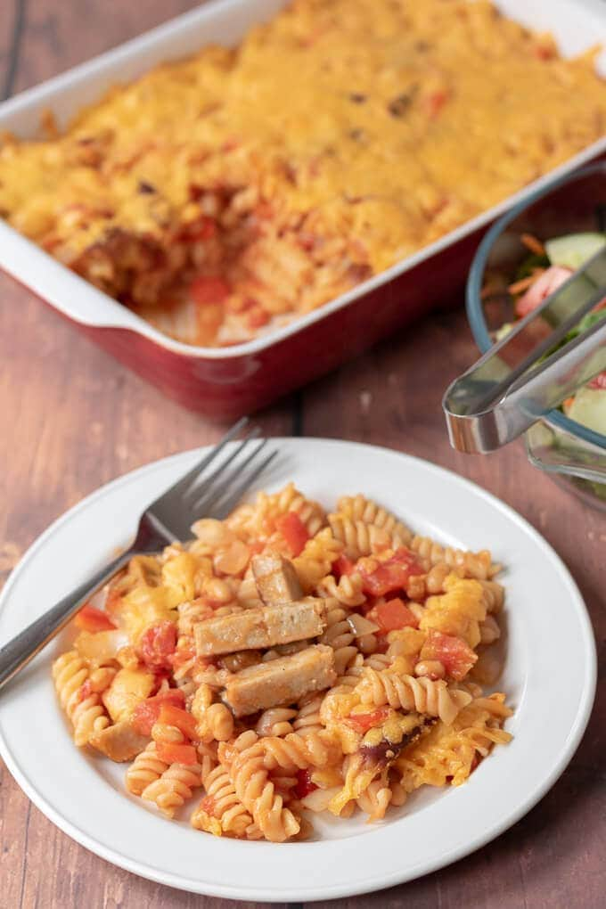 Front view of a plate of sausage pasta bake. Background with casserole dish in and the portion taken out.