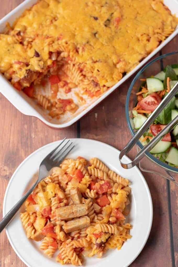 Top down view of sausage pasta bake served in a plate with the whole casserole in the background and a bowl of side salad to share.