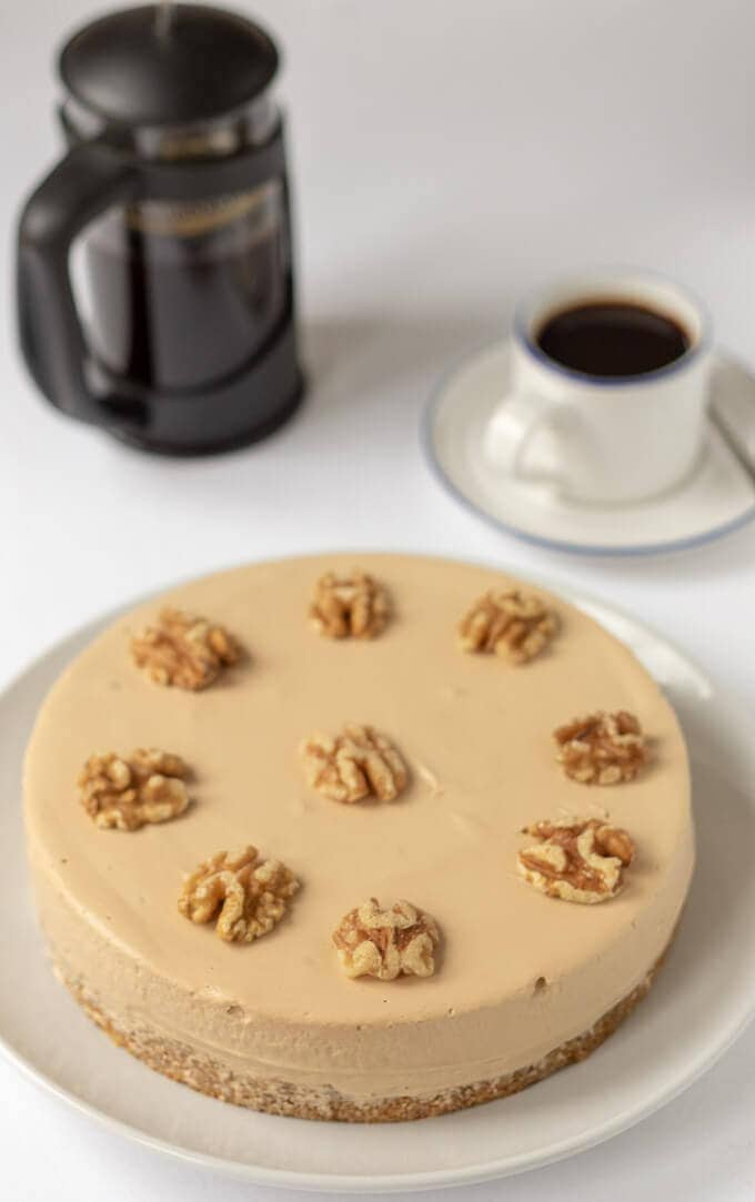 A whole coffee cheesecake just decorated with walnuts on. Coffee cafetière and a cup of coffee in the background.