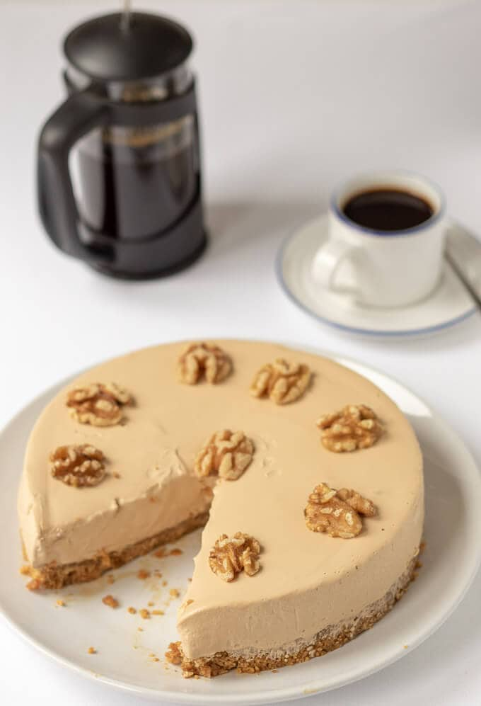 Coffee cheesecake decorated with walnuts and with a slice taken out. Coffee cafetière and a cup of coffee in the background.