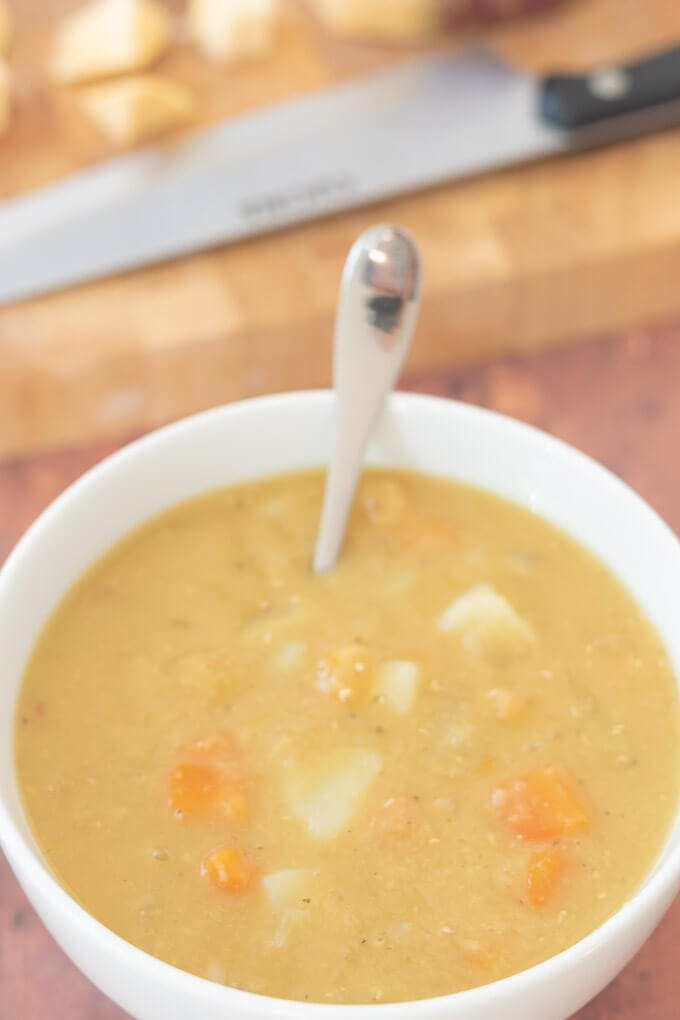 Close up of one bowl of easy Scottish lentil soup with spoon in and chopping board in the background.