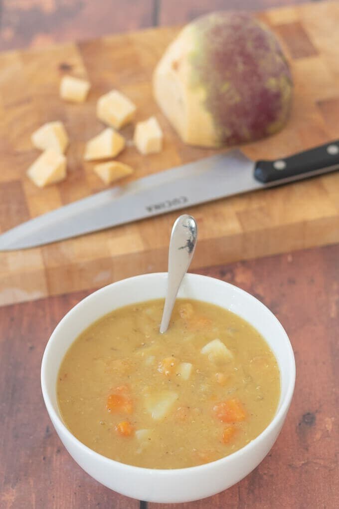 Top down view of easy Scottish lentil soup with chopping board in background with half a turnip on it.