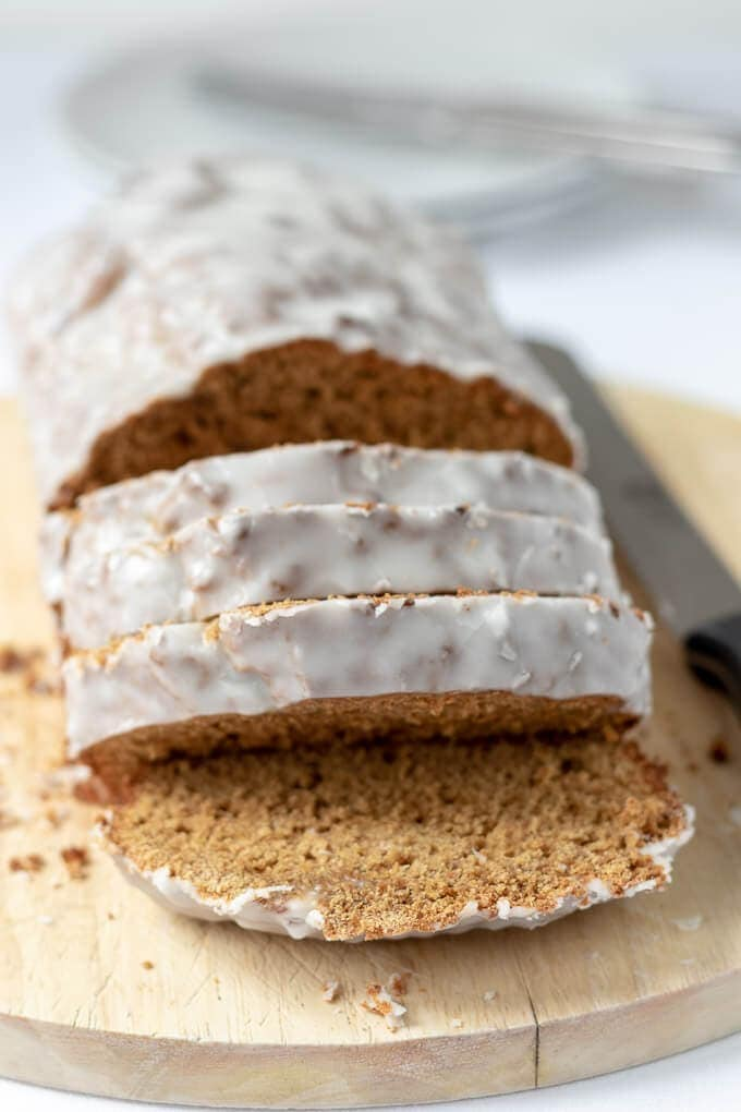 Close up front view of gingerbread loaf cake with 4 slices cut from it.
