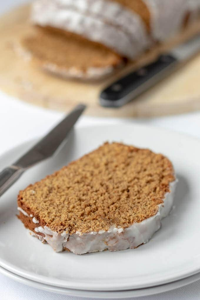 A slice of gingerbread loaf cake on a plate ready to eat with the rest of the sliced loaf in the background.