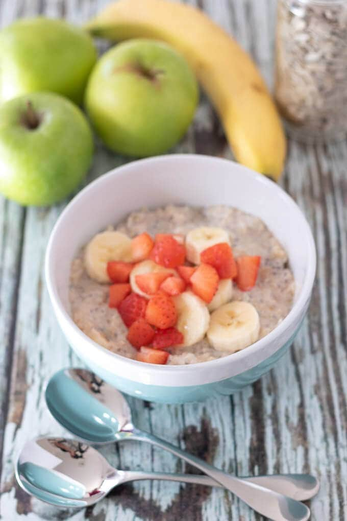 A bowl of quinoa bircher muesli topped with strawberries and ready to eat with apples and a banana for display in the background.