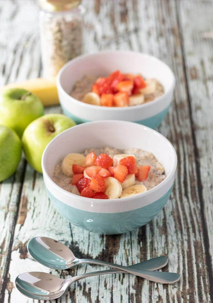 Quinoa bircher muesli in two bowls served and ready to eat. Topped with strawberries and looking delicious!