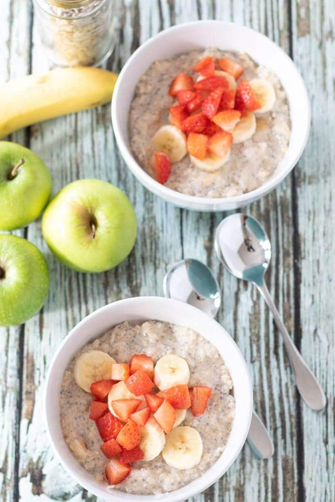 Overhead view of quinoa bircher muesli. 2 bowls of this delicious breakfast topped with strawberries and ready to eat.