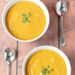 Birds eye view of two bowls of delicious and filling sweet potato and red lentil soup served and ready to eat.