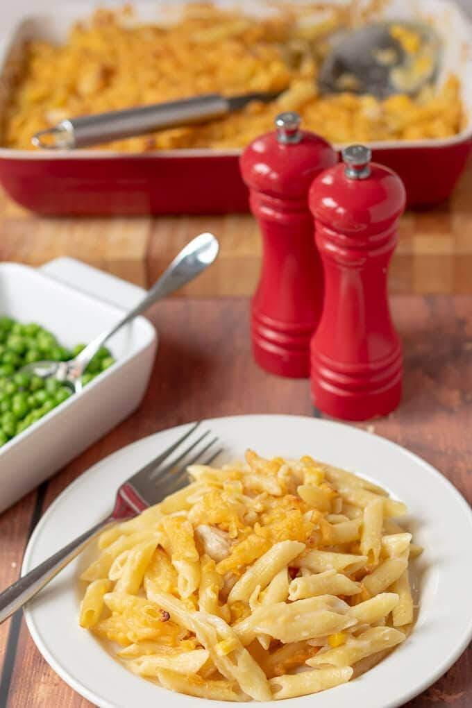 Table view of served chicken and sweetcorn pasta bake on a plate with the casserole in the background and a serving bowl of peas and salt and pepper.