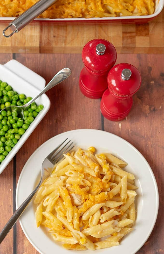 The best chicken and sweetcorn pasta bake served on a white plate with a side of peas beside and salt and pepper shaker behind.