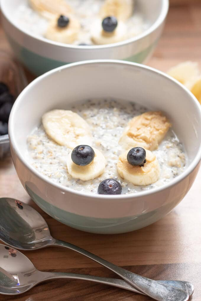World Porridge Day 2018 single bowl of porridge with a smiley face make out of chopped bananas and blueberries.