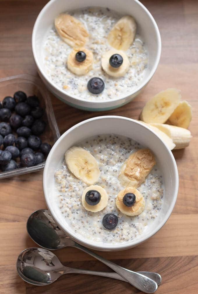 World Porridge Day Bowl of Porridge with smiley face made out of chopped bananas and blueberries.
