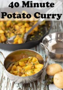 Potato curry served in a Balti dish with the pan of the rest of the cooked curry in the background.