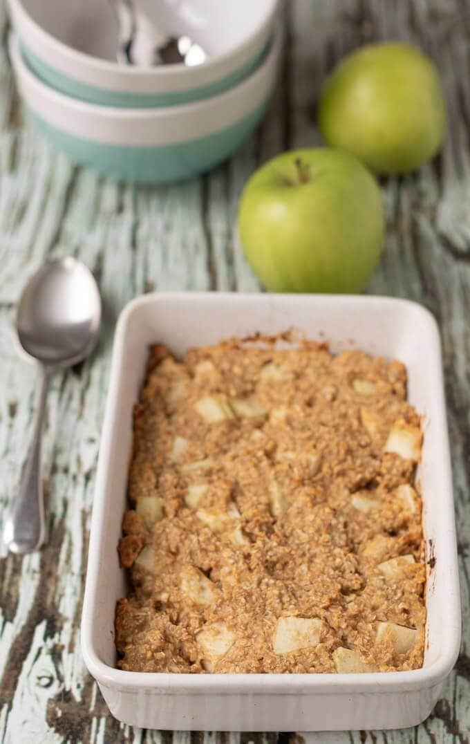 Baked apple and cinnamon oats just out of the oven and presented in casserole dish.
