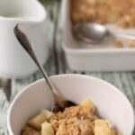 Bowl of cooked baked apple and cinnamon oats served with spoon in.