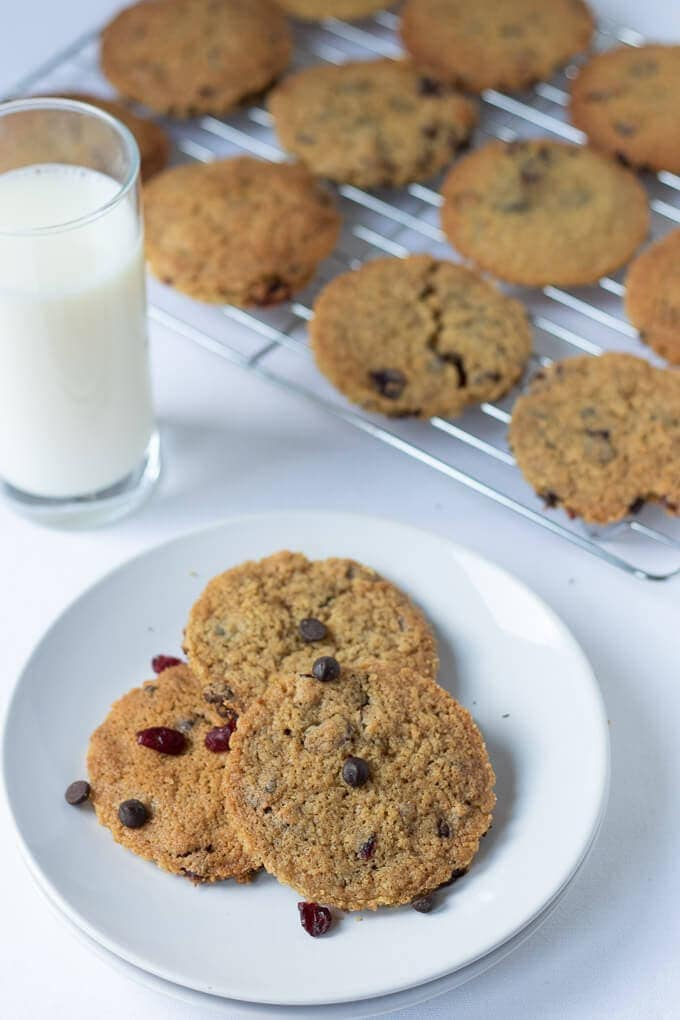 Birds eye view of a plate of 3 dark chocolate chip cranberry cookies served with a glass of milk to the side and the remaining baked cookies on a baking rack behind.