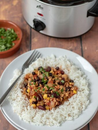 Healthy slow cooker turkey chilli on a plate served on rice and garnished with coriander. Slow cooker in the background with a dish of chopped coriander in between.