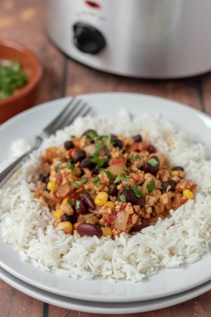 Close up of healthy slow cooker turkey chilli served on rice and garnished with coriander.