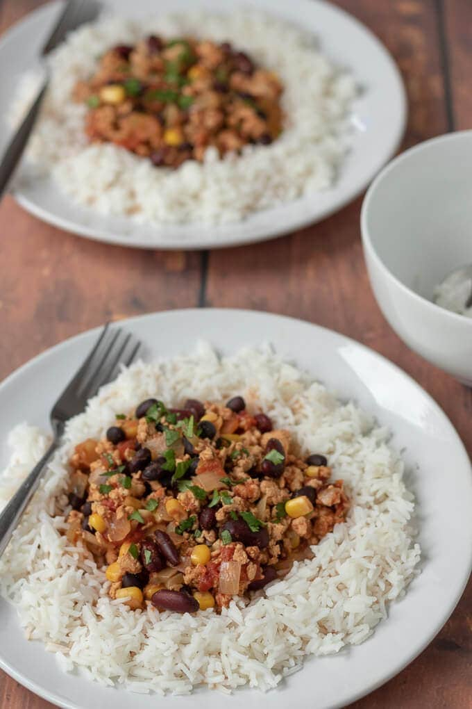 Two plates of healthy slow cooker turkey chilli served on rice and garnished with coriander.
