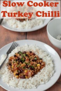 Healthy slow cooker turkey chilli on a plate served on rice and garnished with coriander. Pin title text overlay at top.