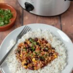 Healthy slow cooker turkey chilli served on rice and garnished with coriander.