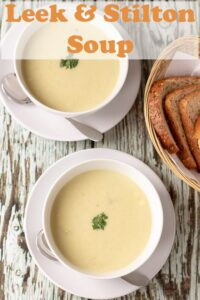 Birds eye view of two bowls of leek and stilton soup. A basket of slices of bread at the side. Pin title text overlay at top.