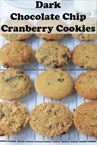A wire baking rack of dark chocolate chip cranberry cookies. Pin title text overlay at top.