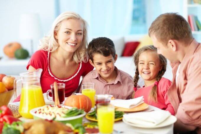 Happy family gathered rounf a table eating out with healthy choices.