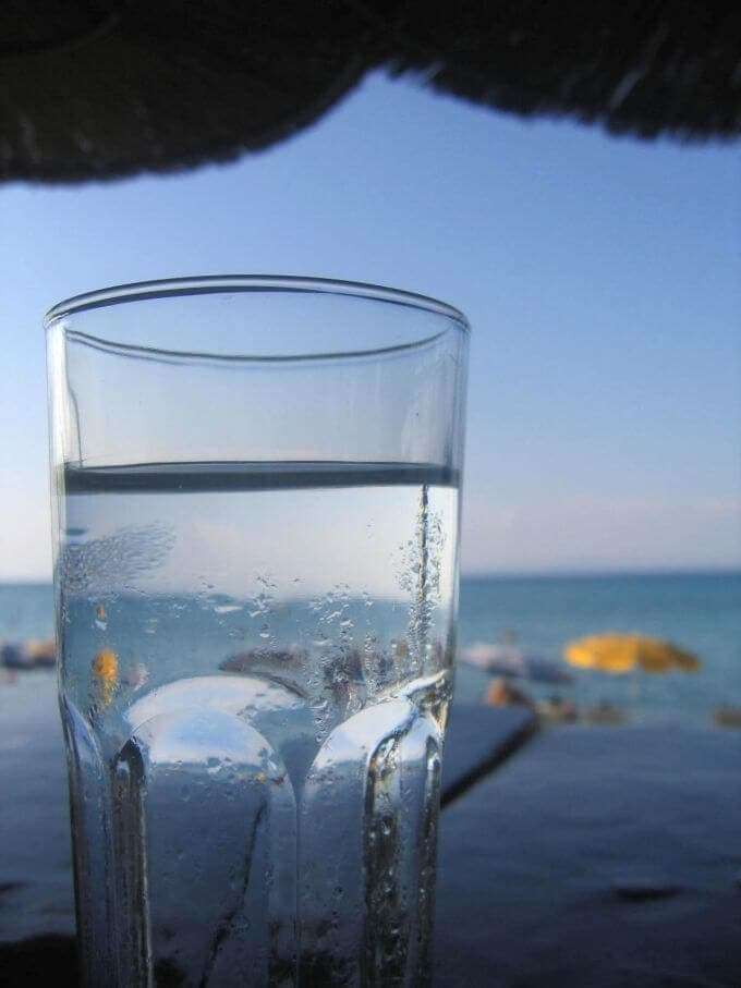 Picture of a glass of water sitting on a table with the sea in the background.