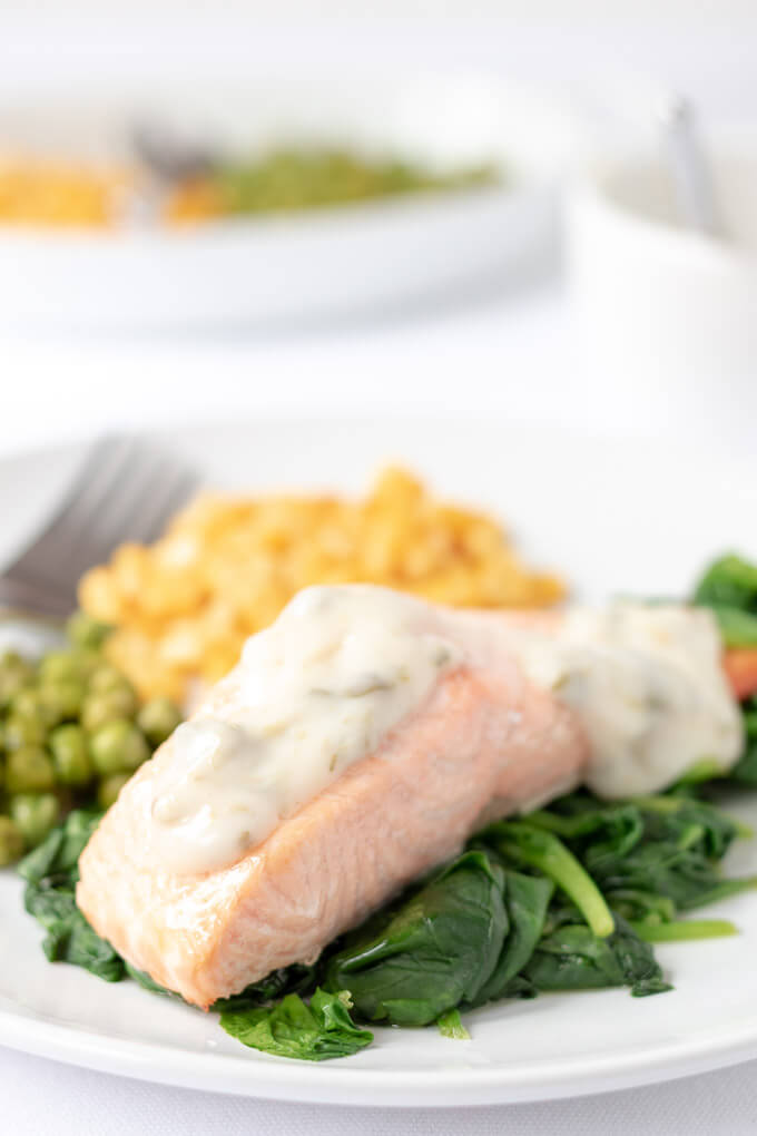 Close up of a plate of healthy grilled salmon on a bed of wlted spinach with a portion of sweetcorn and peas on the plate. Looking delicious and ready to eat!