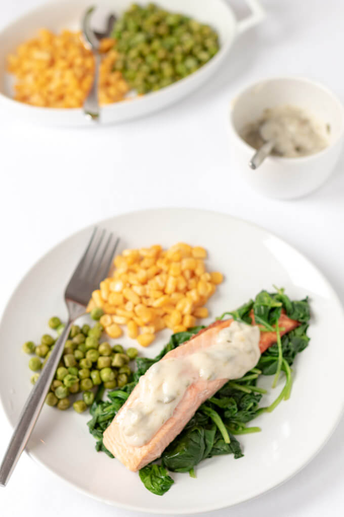 Birds eye view of a plate of healthy grilled salmon with a healthy marinate on top and served with peas and sweetcorn.