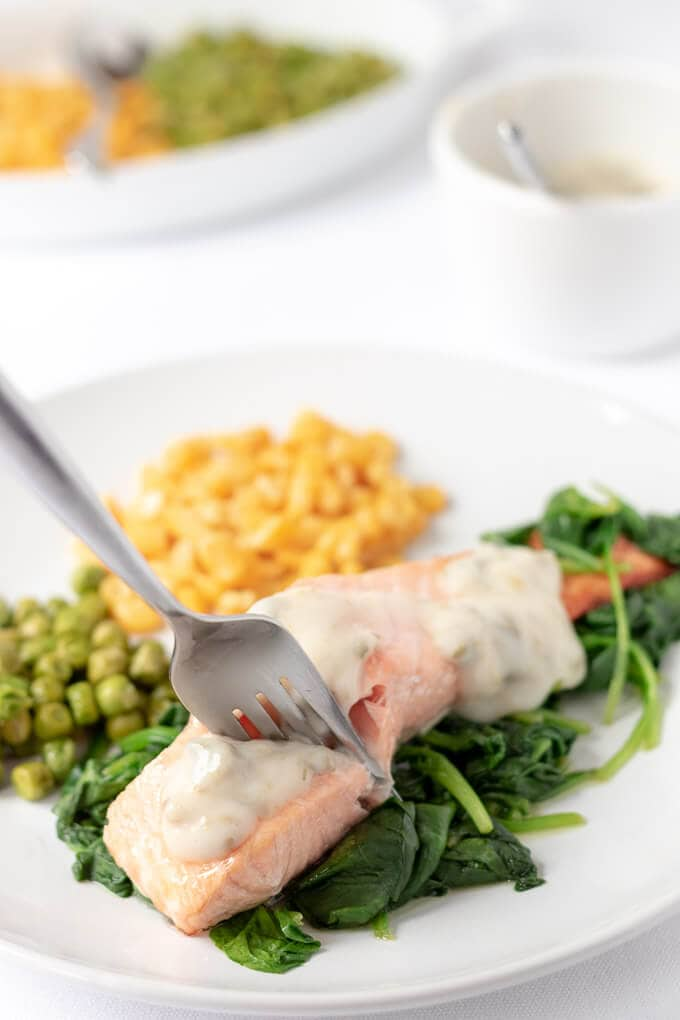 A fork stuck into a grilled salmon filled on a bed of wilted spinach with a portion of peas and sweetcorn ready to eat.
