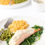 Healthy grilled salmon served on a bed of wilted spinach with a portion of sweetcorn and peas on a plate.