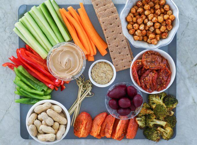 Picture of healthy snacks featuring carrot sticks, celery sticks, hummus, chicpeas and nuts.