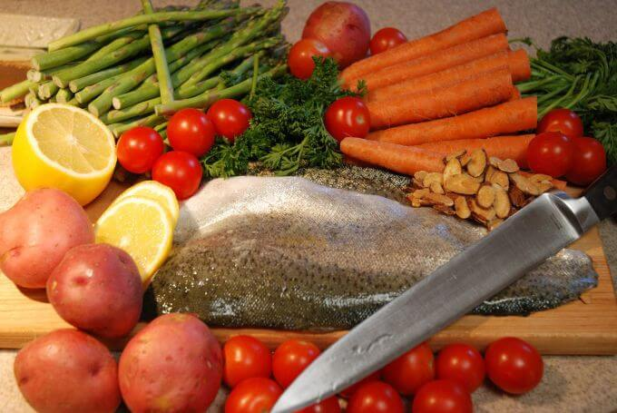Ingredients for a meal featuring fish and a selection of vegetables.