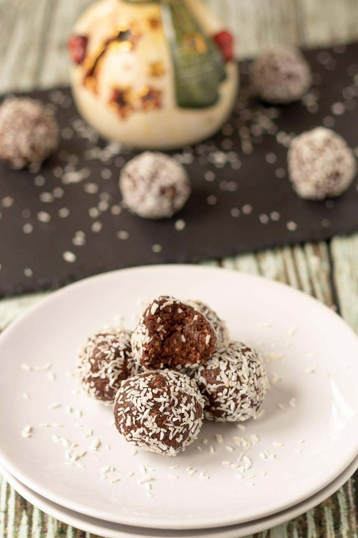 A plate of five delicious mums no bake chocolate snowballs piled up on a plate with a bite taken out of the top snowball. Rest of the snowballs on a black slate in the background.