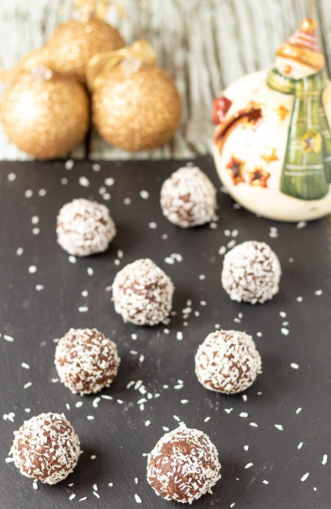 Mum's no-bake chocolate snowballs rolled and ready to eat displayed on a black slate with Christmas decorations in the background.