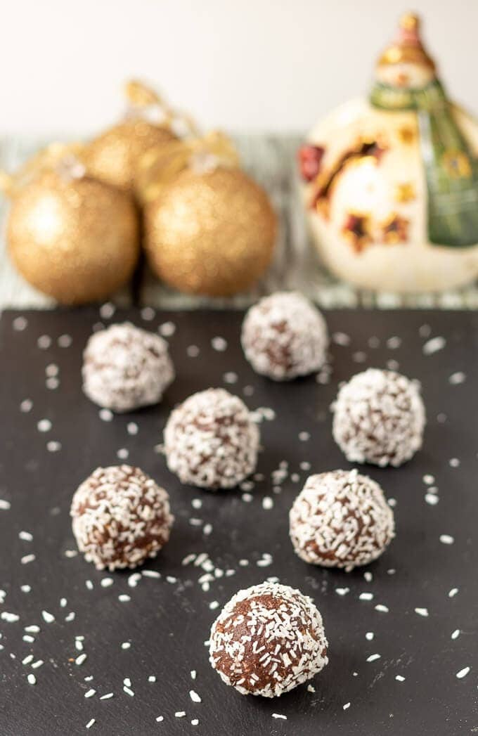 Mum's no-bake chocolate snow balls displayed on black slate looking delicious with Christmas decorations in the background.
