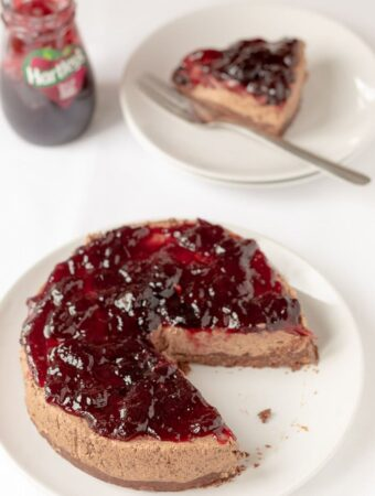 Delicious no-bake black cherry chocolate cheesecake on a plate with a slice taken out of it and placed on a plate to the rear with a serving fork on. A jar of jam to the left side.