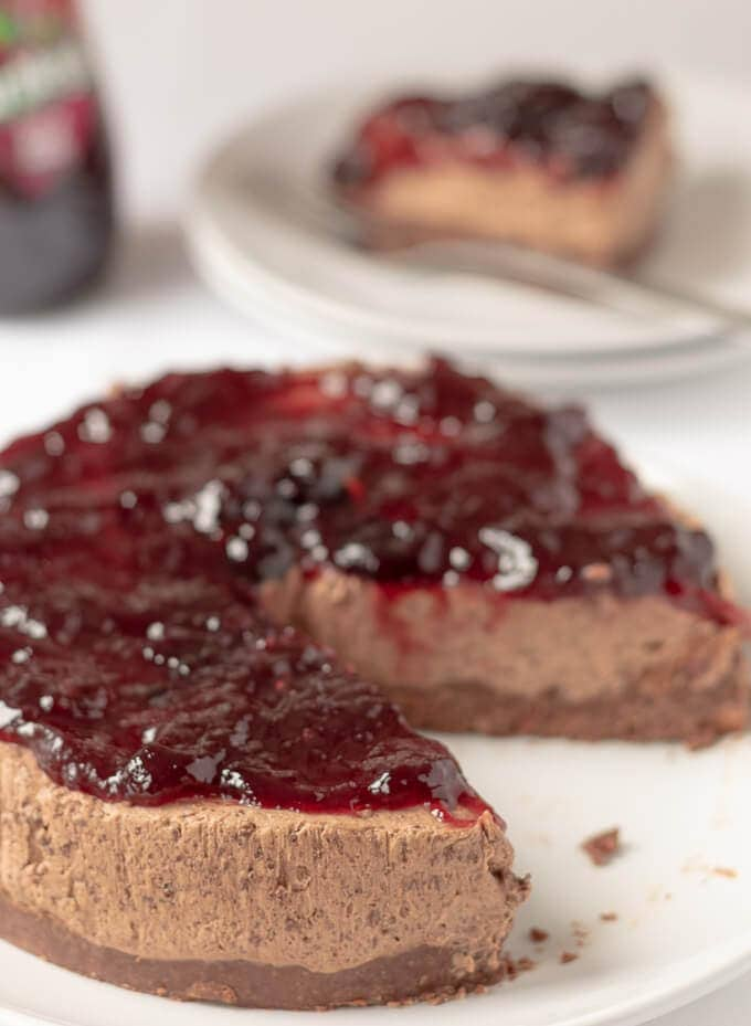 Close up of no-bake chocolate cheesecake on a white plate with a slice of cheesecake and jar of black cherry jam in the background.