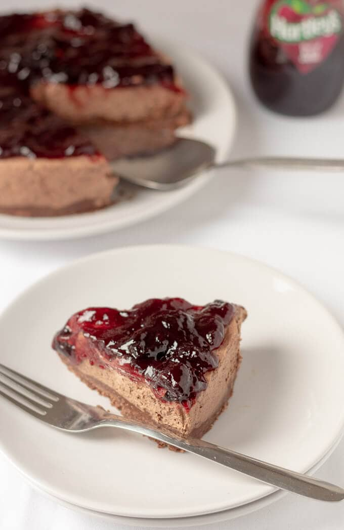 A single slice of no-bake black cherry chocolate cheesecake on a plate in front of the main cheesecake.