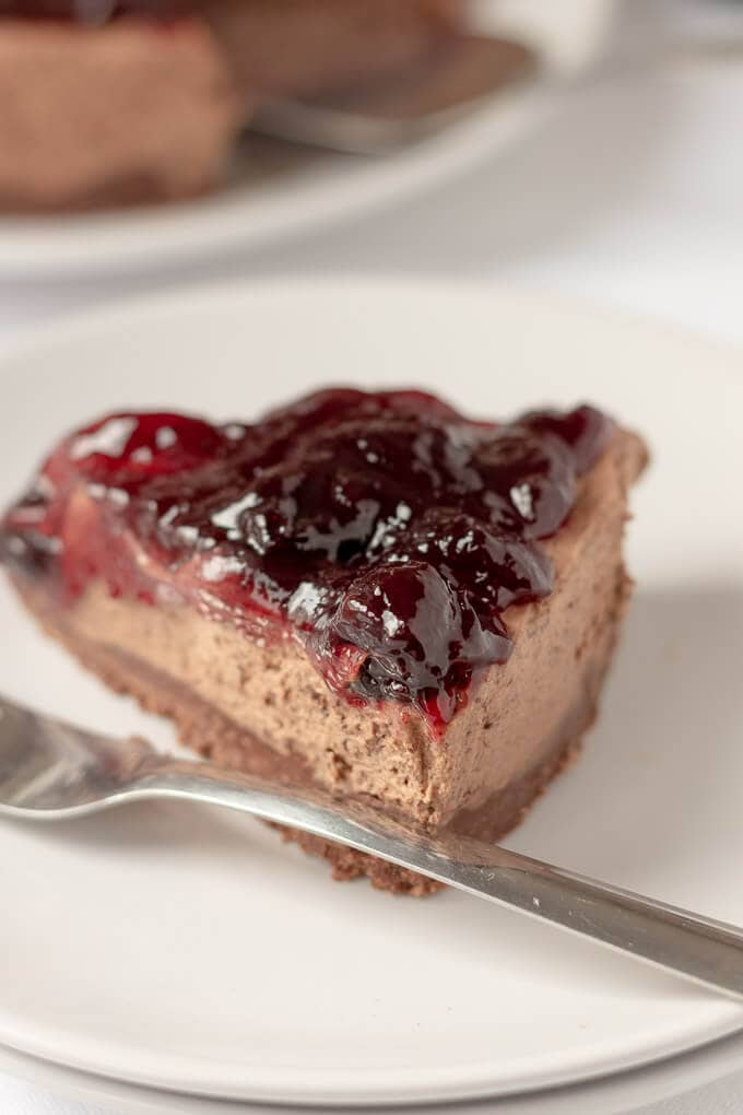 Close up a a single slice of delicious no-bake black cherry cheesecake.