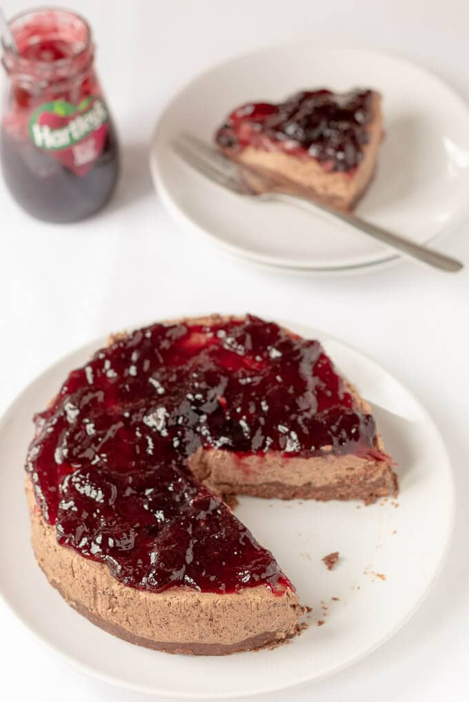 Delicious no-bake black cherry chocolate cheesecake on a plate with a slice taken out of it and placed to the rear.
