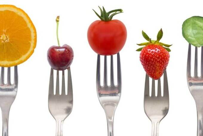 Forks with vegetables and fruits on.