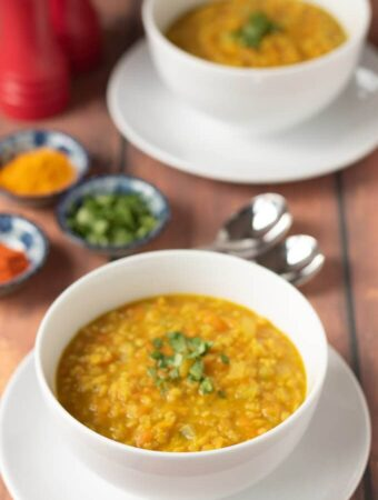 Two delicious bowls of curried red lentil soup with a selection of spices in seperate bowls in between.