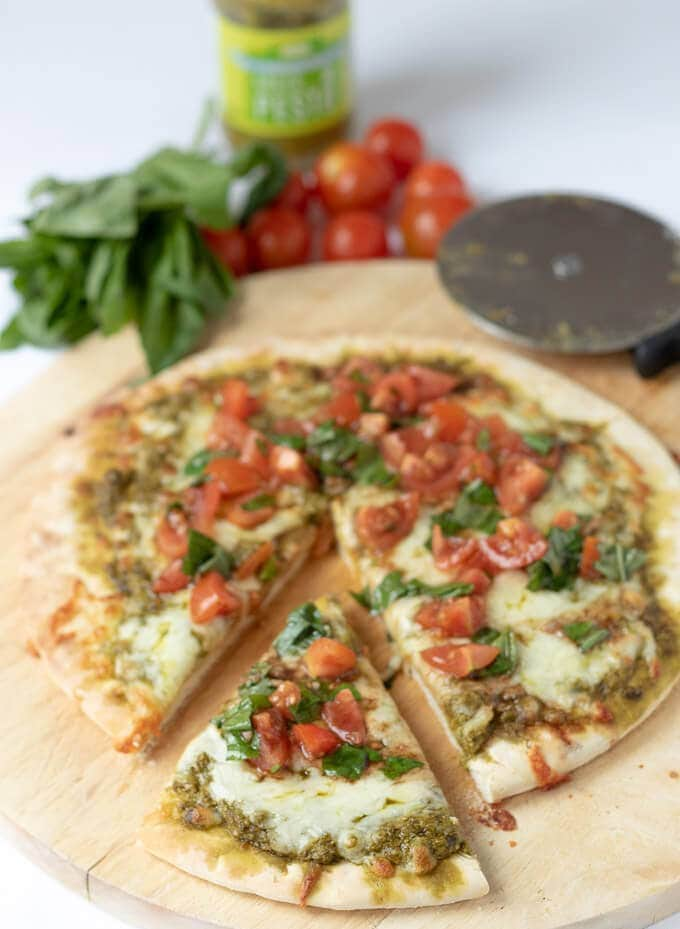 A closer view of the delicious pesto pizza on a chopping board with a slice taken out of it.