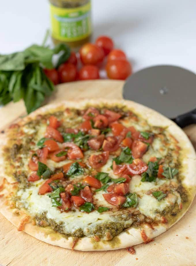 A delicious pesto pizza cooked sitting on a chopping board, ready to carve into slices and eat with cherry tomatoes and basil in the background for decoration.