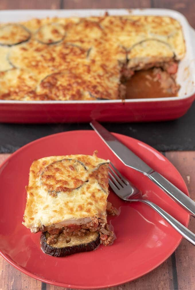 A cut slice of healthier Moussaka on a plate taken from the main casserole dish in the background looking delicious and ready to eat.